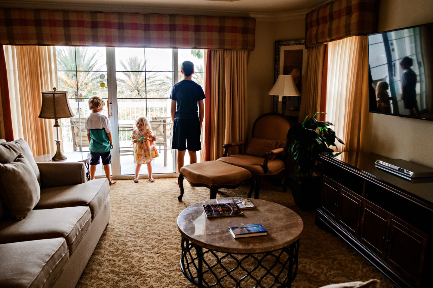 Reunion Resort by popular Atlanta travel blog, Chelissima: image of Chelsea Patricia's children looking out the window of their Reunion Resort room.