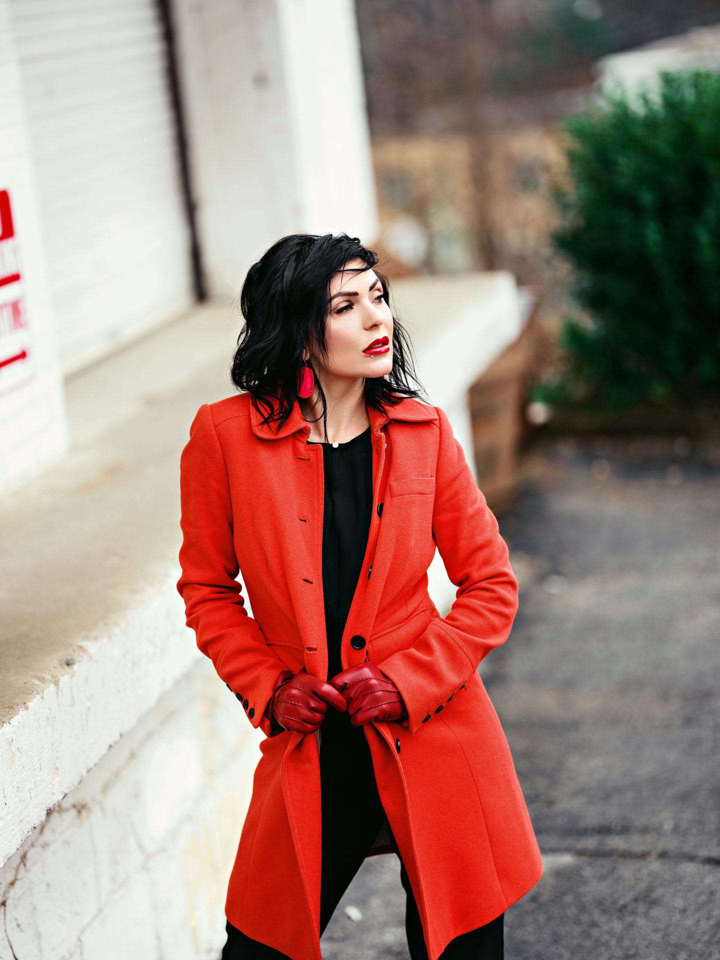 Stylish work outfits featured by top US fashion blogger, Chelissima: image of a woman wearing a red JCrew peacoat, black jumpsuit, Coach red leather gloves, and Kendra Scott jewelry